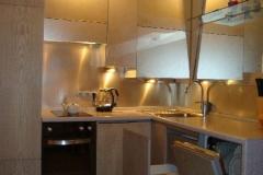 Кухня угловая со встроенной техникой. Фасады внизу - шпон дерева.Фасады вверху - зеркало уади серебро в алюминиевой рамке.
