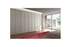 Белый шкаф с распашными дверками в спальне.