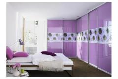 Встроенный угловой шкаф в спальне. Двери купе с нижне опорной алюминиевой системой , Вставки из трёх сегментов. Стекло сиреневого цвета и в тон фотопечать с рисунком цветы