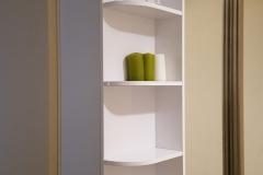 Угловой элемент зеркального шкафа с открытыми радиусными полками и шкафчиком за распашной дверкой