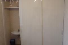 Встроенный в постирочной комнате шкаф с раздвижными дверями из влагостойкого лдсп