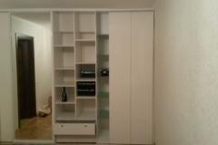 Встроенный шкаф с одной раздвижной, зеркальной дверью и распашными дверками из белого гянца