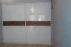 Встроенный шкаф. Раздвижные двери в алюминиевом профиле со вставками из глянцевого белого стекла и дерева