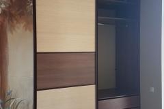 Раздвижные дверки со вставками из бамбука. Внутри выдвижные ящики, полки и штанги для одежды.